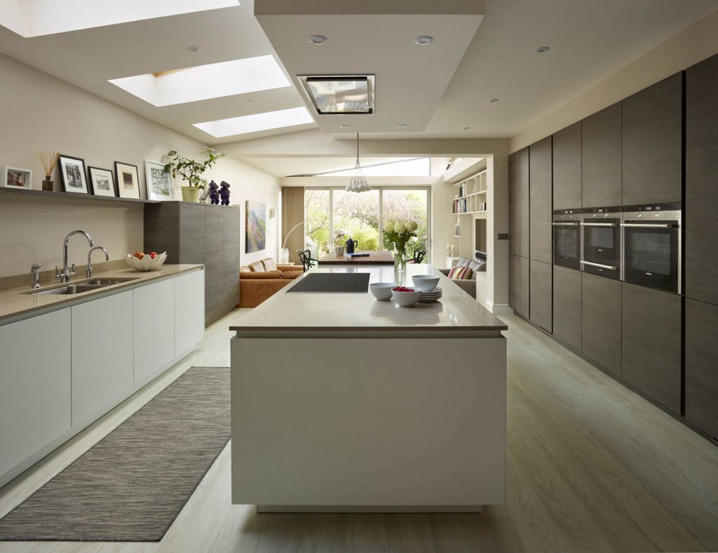 Long view of modern open plan kitchen in a white base unit finish with light brown porcelain worktops and living space at the rear