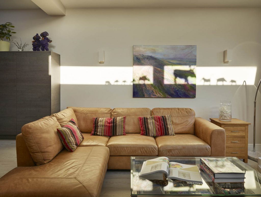 Living space with light brown sofa and glass coffee table
