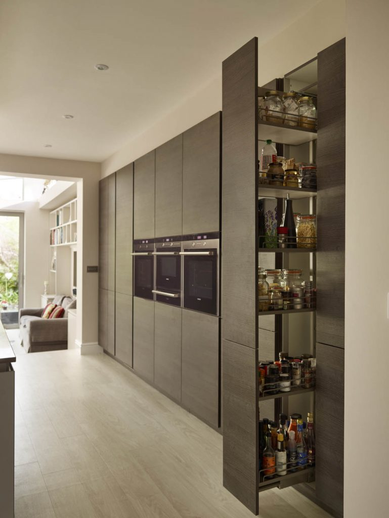 Dark brown tall storage units displaying pull out larder unit