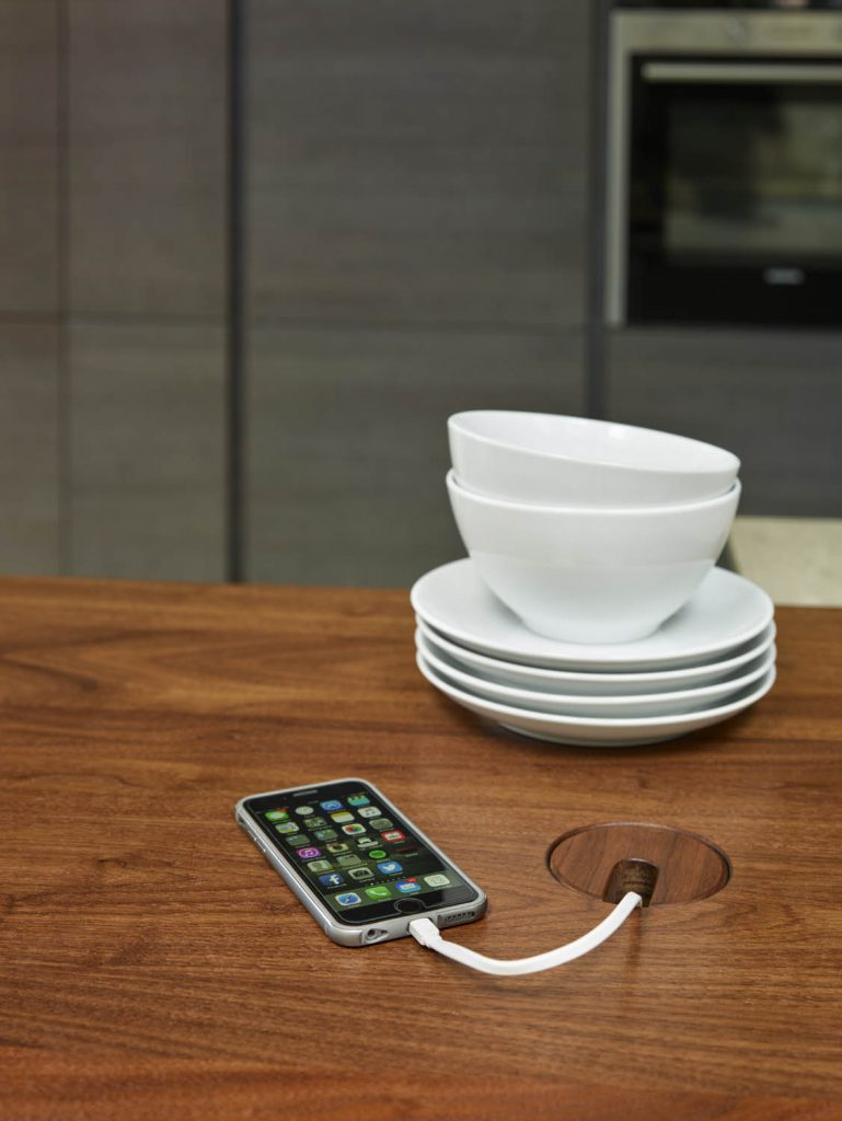Walnut tabletop with bowls and plates placed on top along aside a phone charging through a special port integrated into table unit