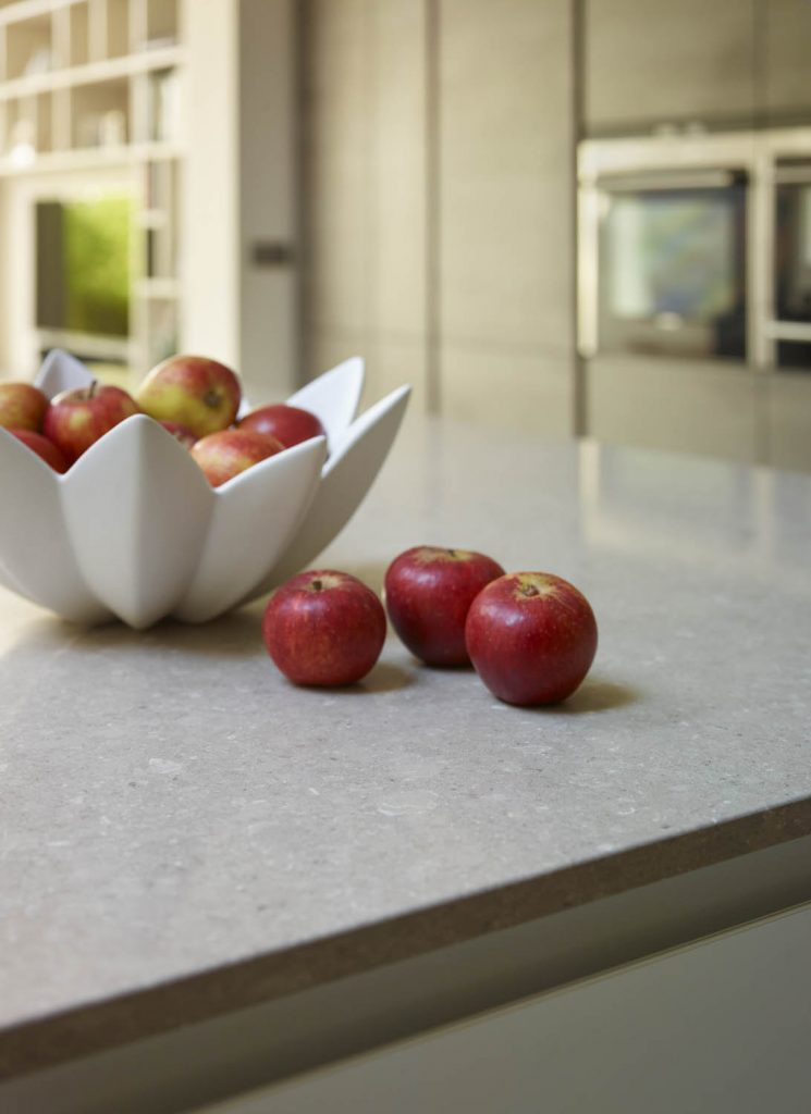 Bowl of apples resting on-top of light brown porcelain work-surface