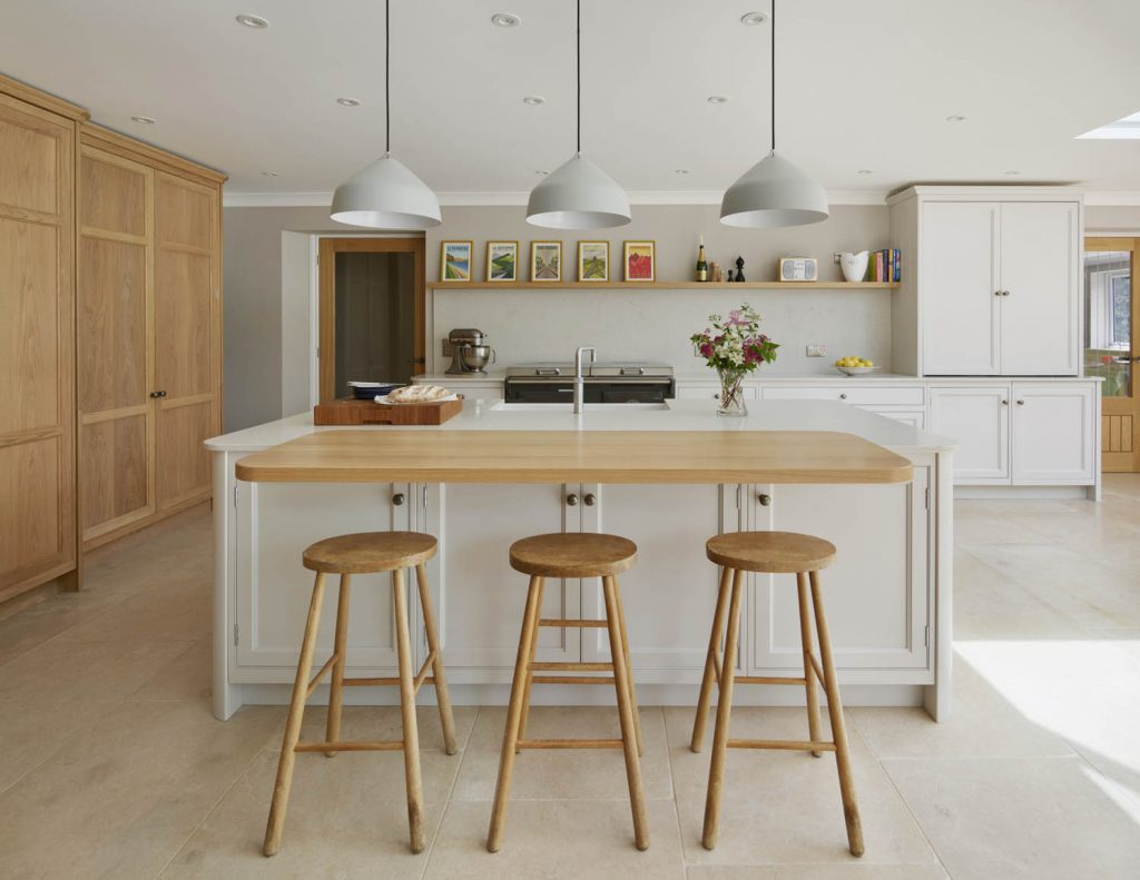 Modern and traditional style island with composite worktop and oak overhanging casual seating area