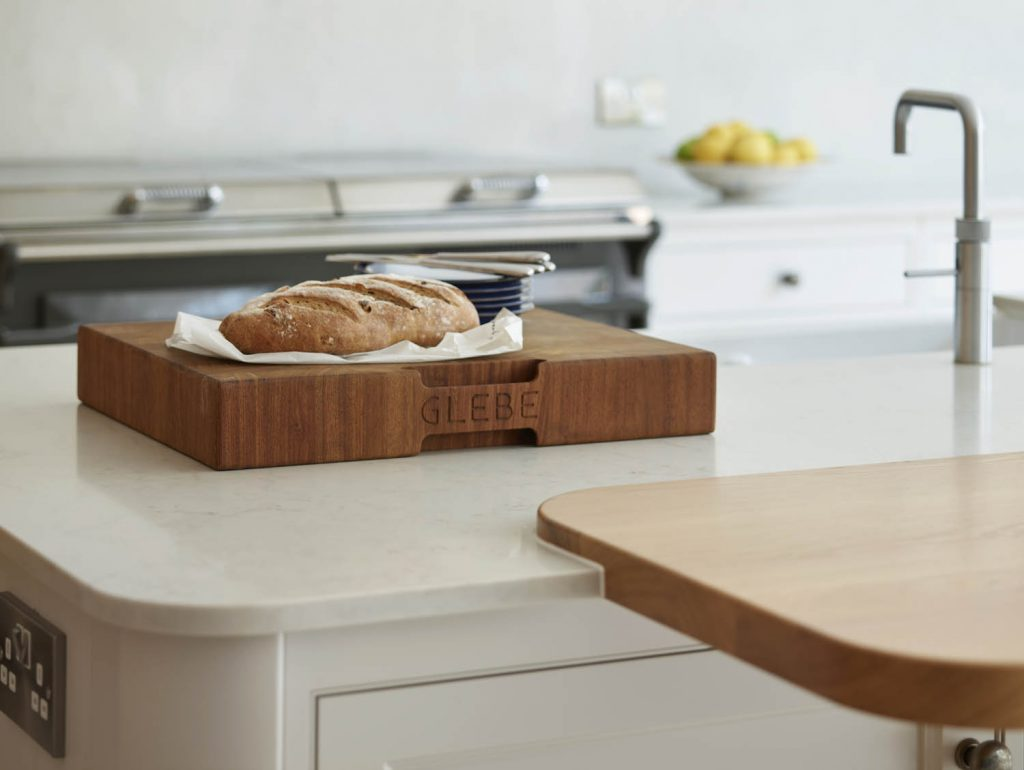 Loaf of bread on a chopping board placed on white composite worktop