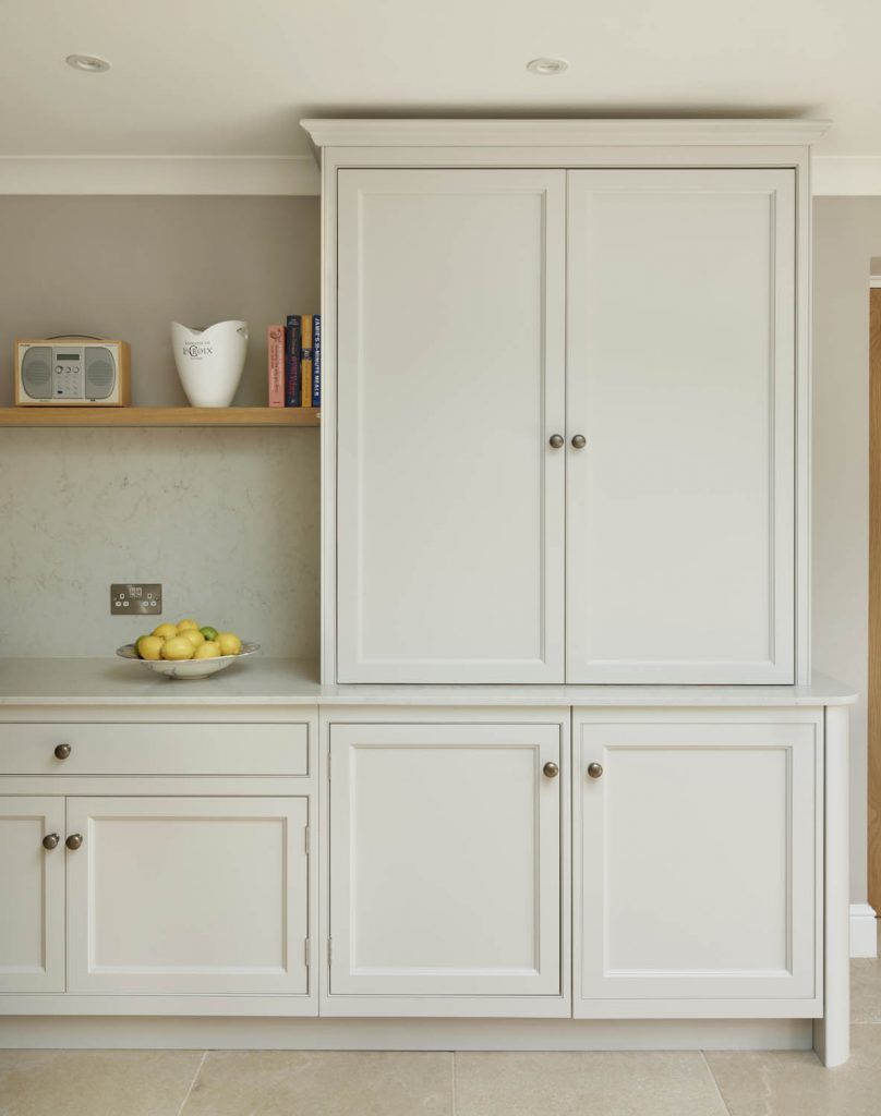 Modern and traditional style base and overcounter kitchen cabinets in white wood finish to match a white composite worktop