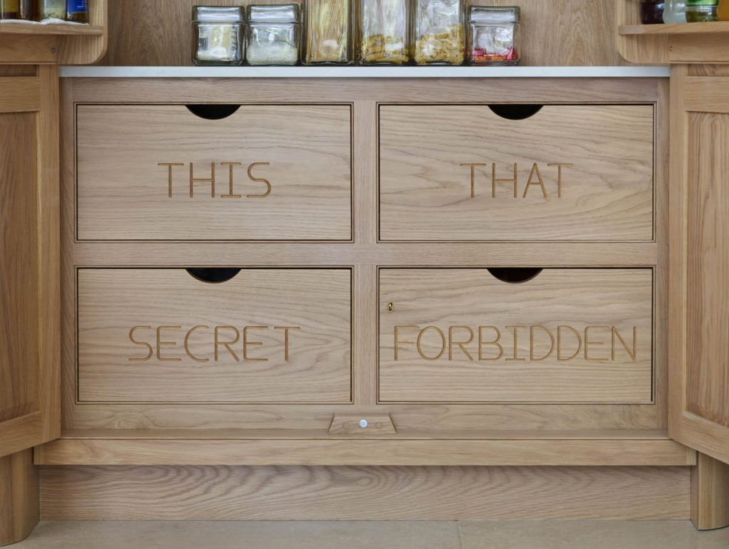 Custom oak larder unit with four inside drawers beneath white composite worktop