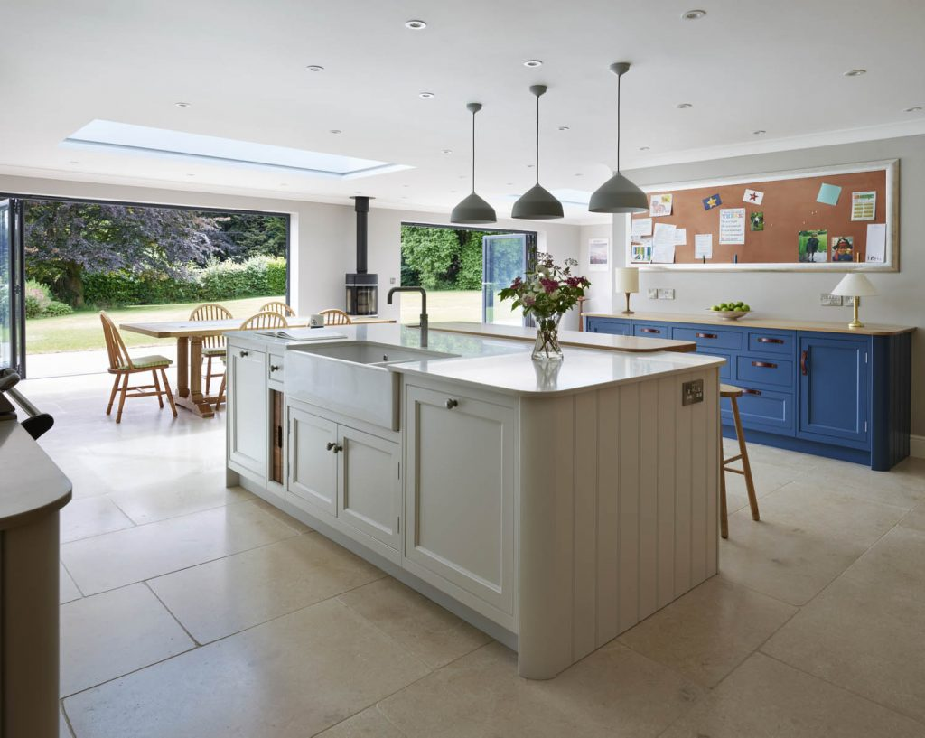 Modern and traditional style kitchen island with white wood base units and white composite worktop