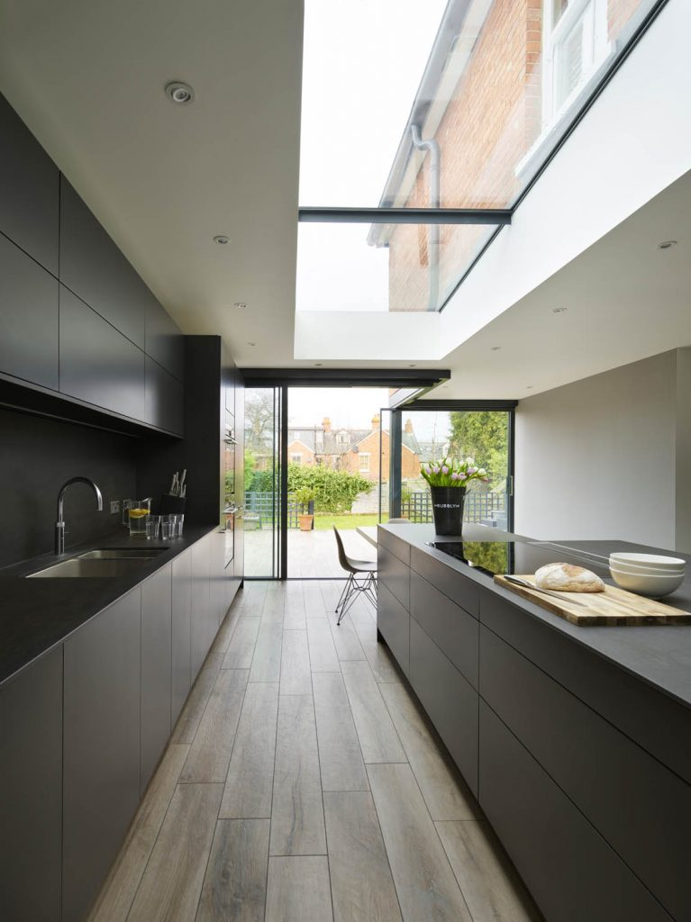 Modern, contemporary kitchen showing island with matching tall units, both finished with a dark porcelain worktop
