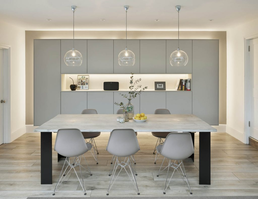 Modern, contemporary kitchen showing white oak six seater dining table infont of tall white cabinets