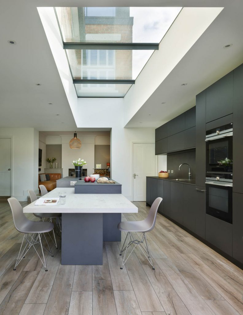 Modern, contemporary kitchen with abstract island in a white and dark grey finish with casual seating and Gaggenau appliances