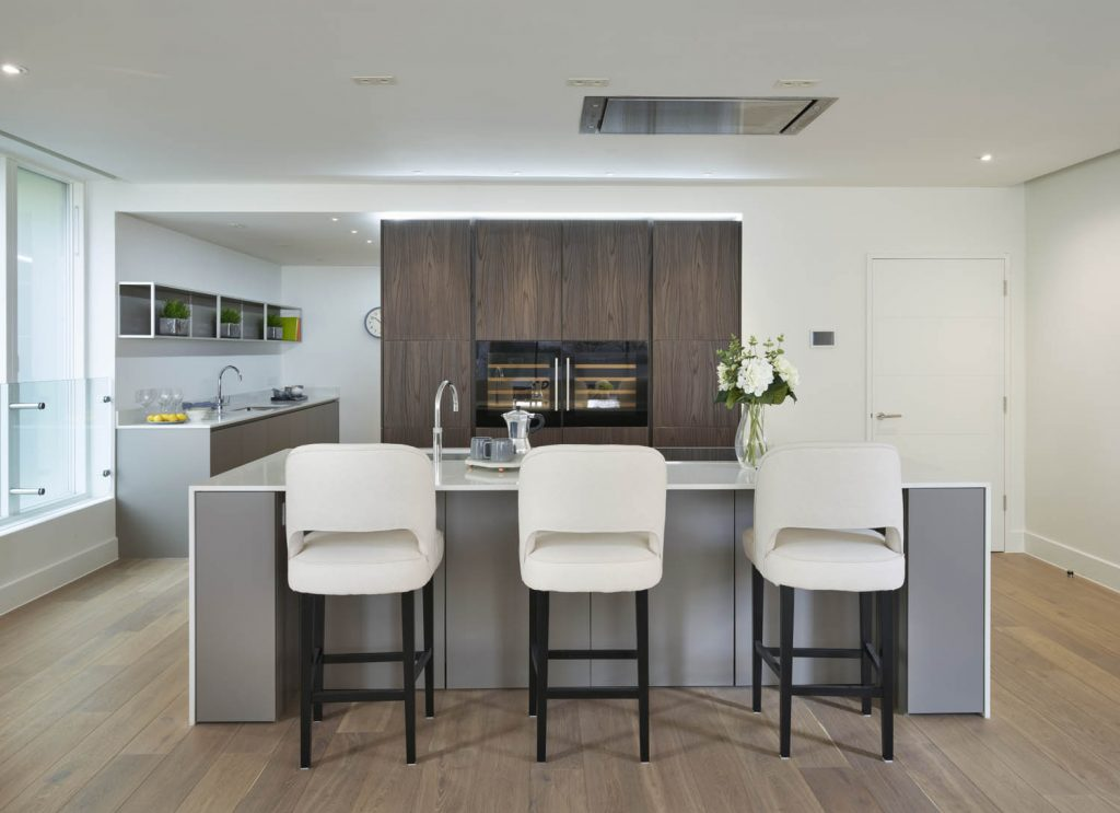 Open plan shot of kitchen with dark brown timber tall units and white porcelain high casual seating arrangement