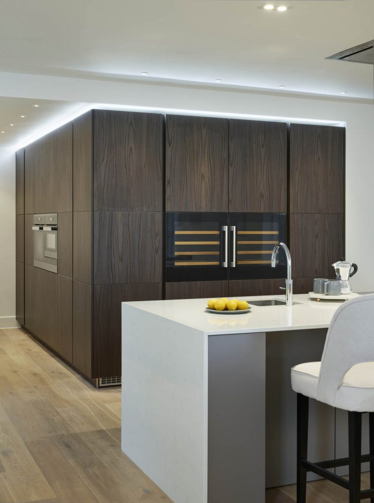 Kitchen with dark brown tall timber finish storage units with white porcelain island and high seating