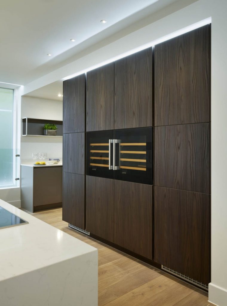 Dark brown tall kitchen storage units with centered appliances