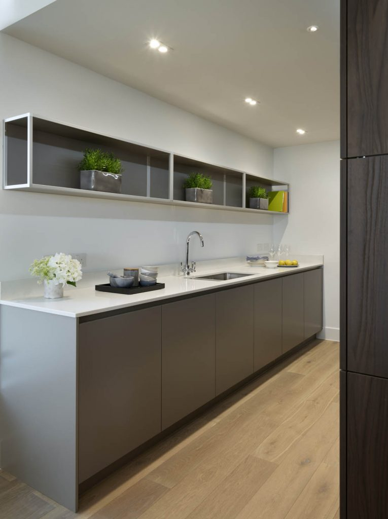 Utility space with grey base units and white worktop as well as custom hanging shelving above