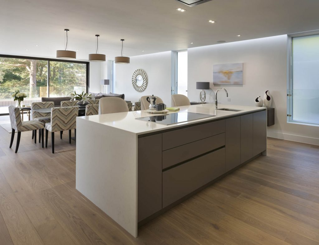 Open view of contemporary kitchen with white porcelain island with down-stand's and high seating and living space in the background