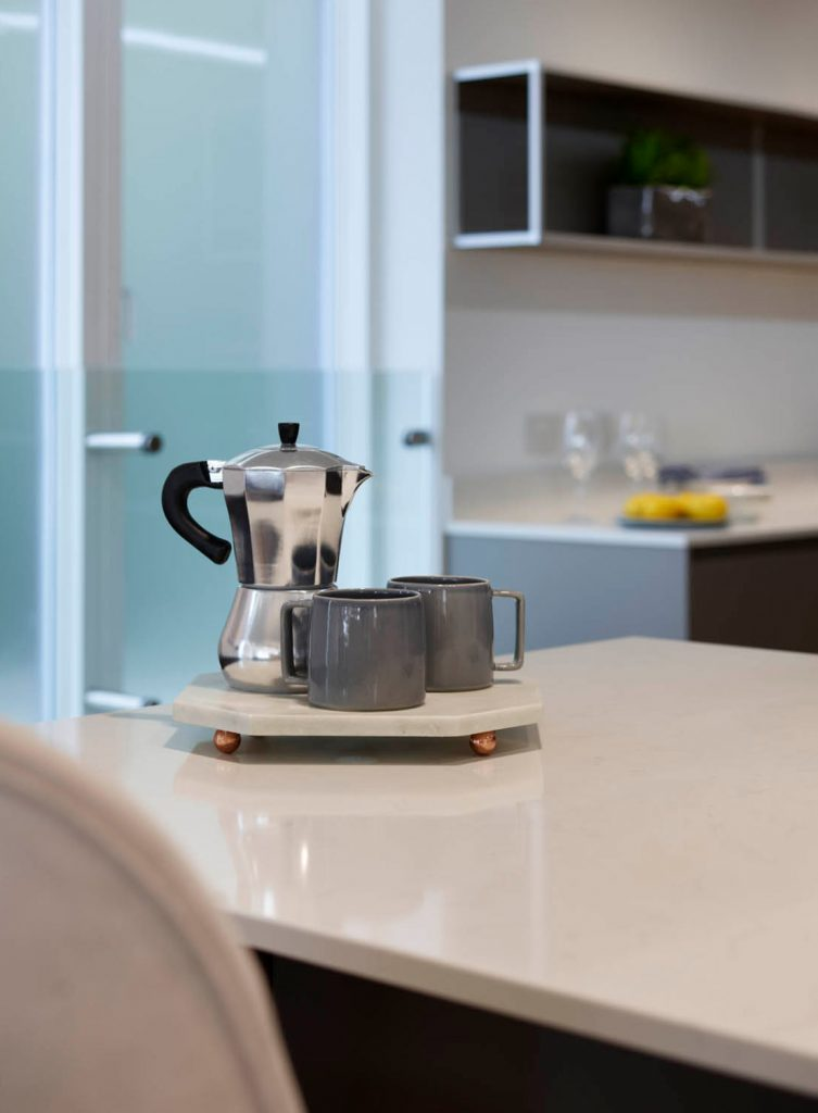 White porcelain island worktop with kettle and two mugs on work-surface