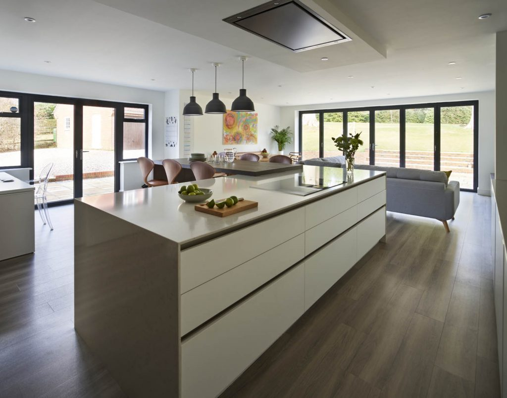 Wide view of contemporary open plan kitchen and living space with porcelain white counter-tops and dark brown timber high tabletops coupled with living room seating area