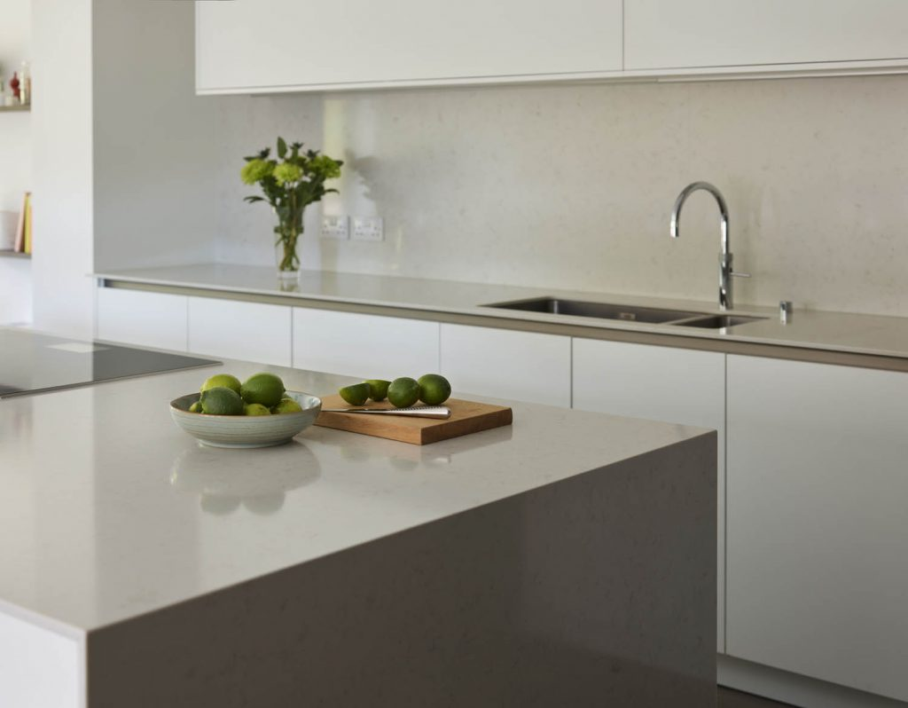 Bowl of Limes positioned on white porcelain worktop with chopping board next to Gaggenau hob opposite sink