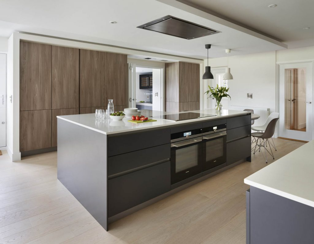 Wide view of white porcelain island and dark navy base units situated in open plan kitchen