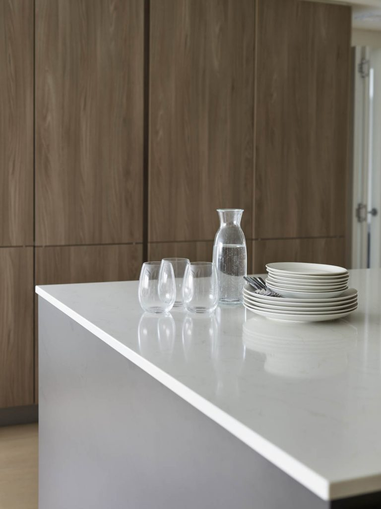 Dark brown timber tall storage units with three glasses, plates and water jug on white porcelain counter-top