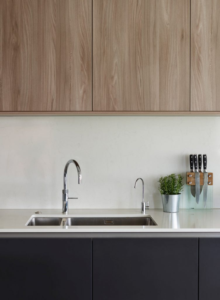 Over-counter timber wall units above white porcelain work-top with installed sink and dark navy base units