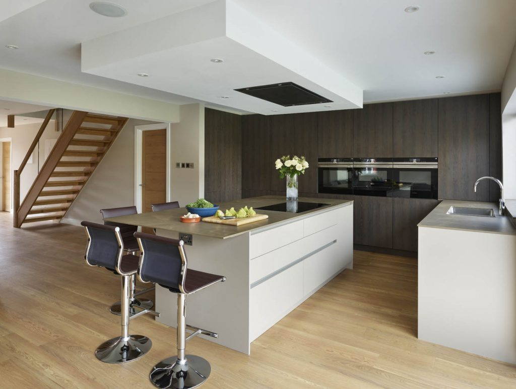 Modern, contemporary kitchen featuring island with white units and porcelain worktop and casual bar seating and tall units with built in Gaggenau appliances and a wood finish