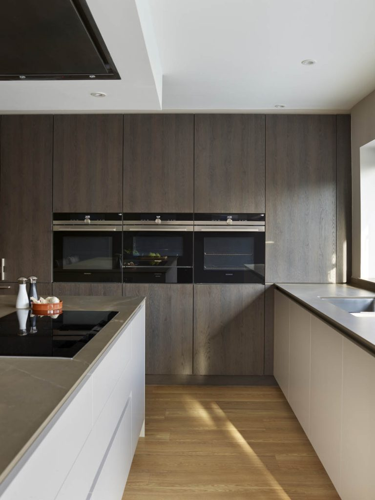 Modern, contemporary kitchen featuring tall units with built in Gaggenau appliances and a wood finish