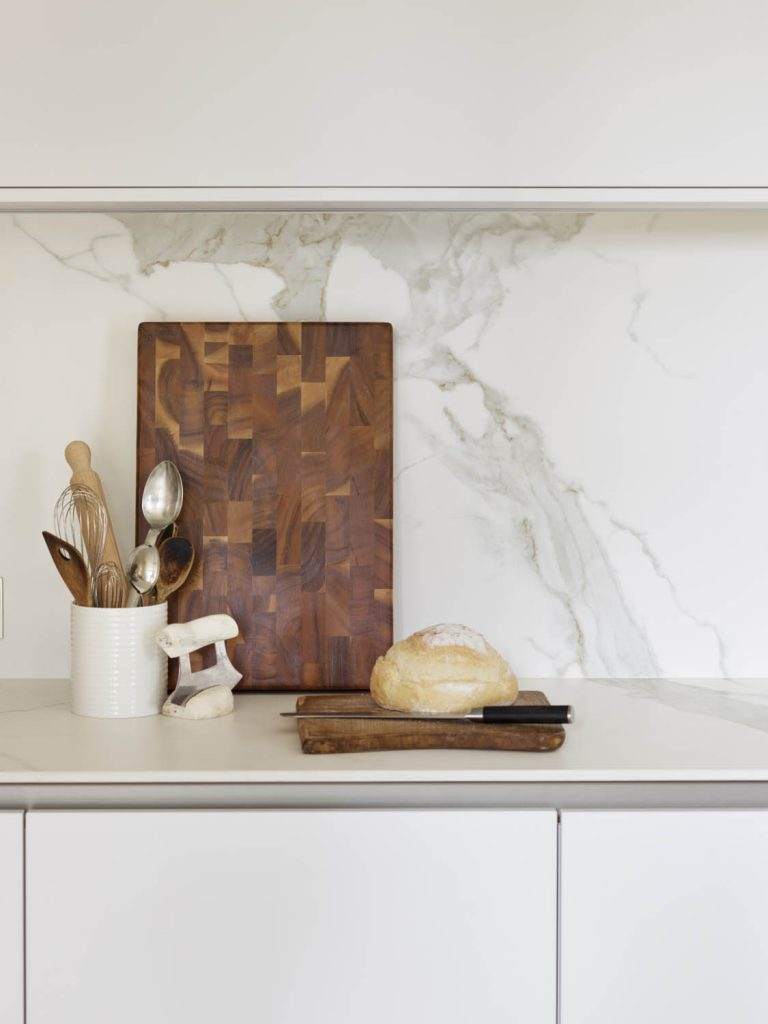 Wide shot of bread and chopping board on porcelain worktop
