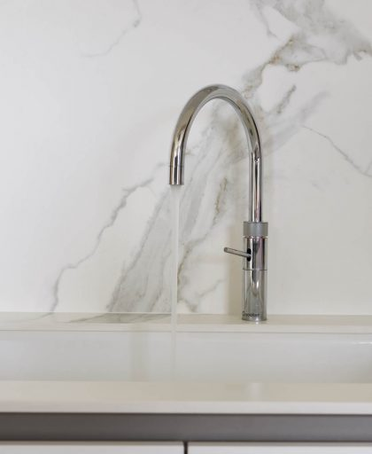 Tap for kitchen sink with marble porcelain splashback