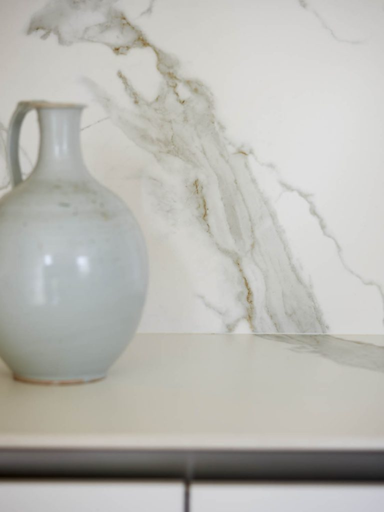Porcelain splashback with marble effect and vase in foreground