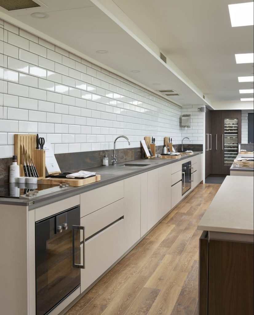 Contemporary kitchen showing run of kitchen units and island finished with porcelain worktops and built in Gaggenau appliances