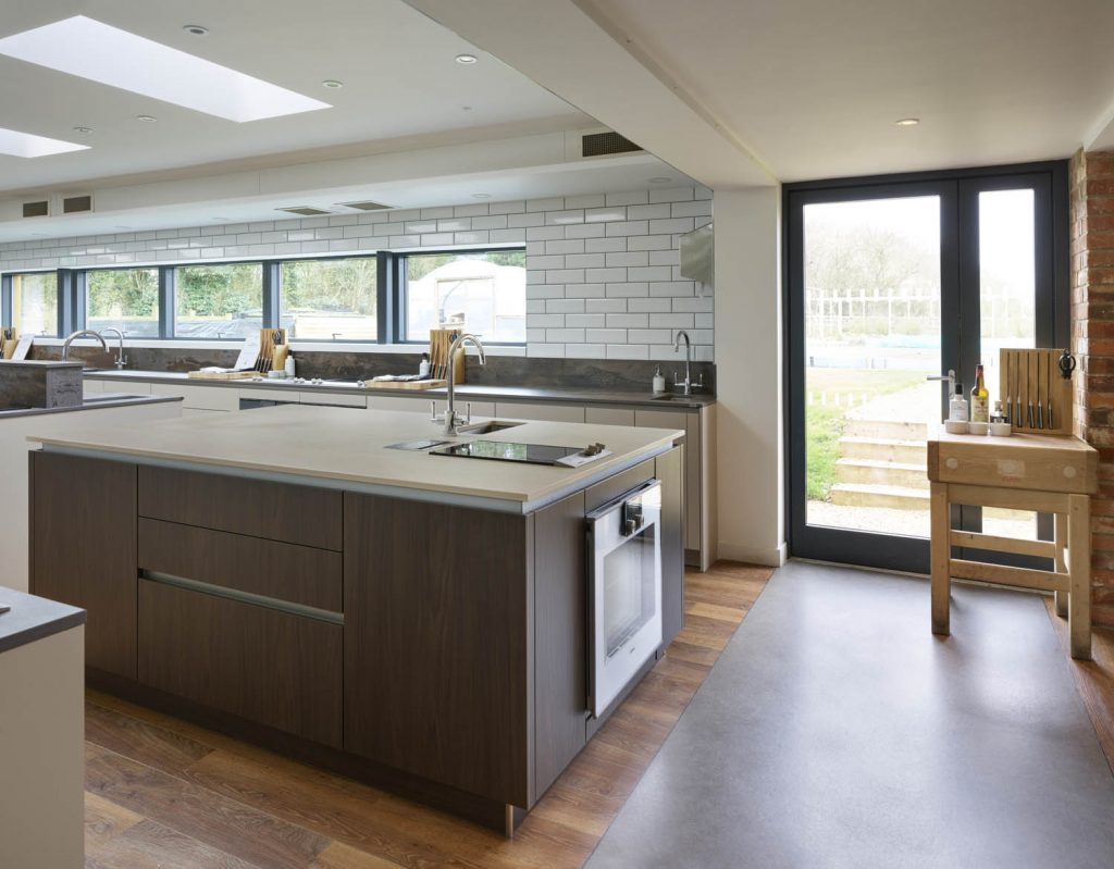 Contemporary kitchen including Gaggenau appliances on a porcelain finsihed island