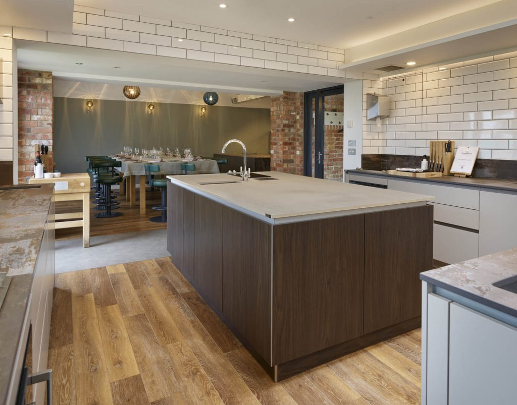 Contemporary kitchen Island with wooden units and a light coloured porcelain worktop, overlooking table at the Woodspeen cookery school in Newbury, Berkshire