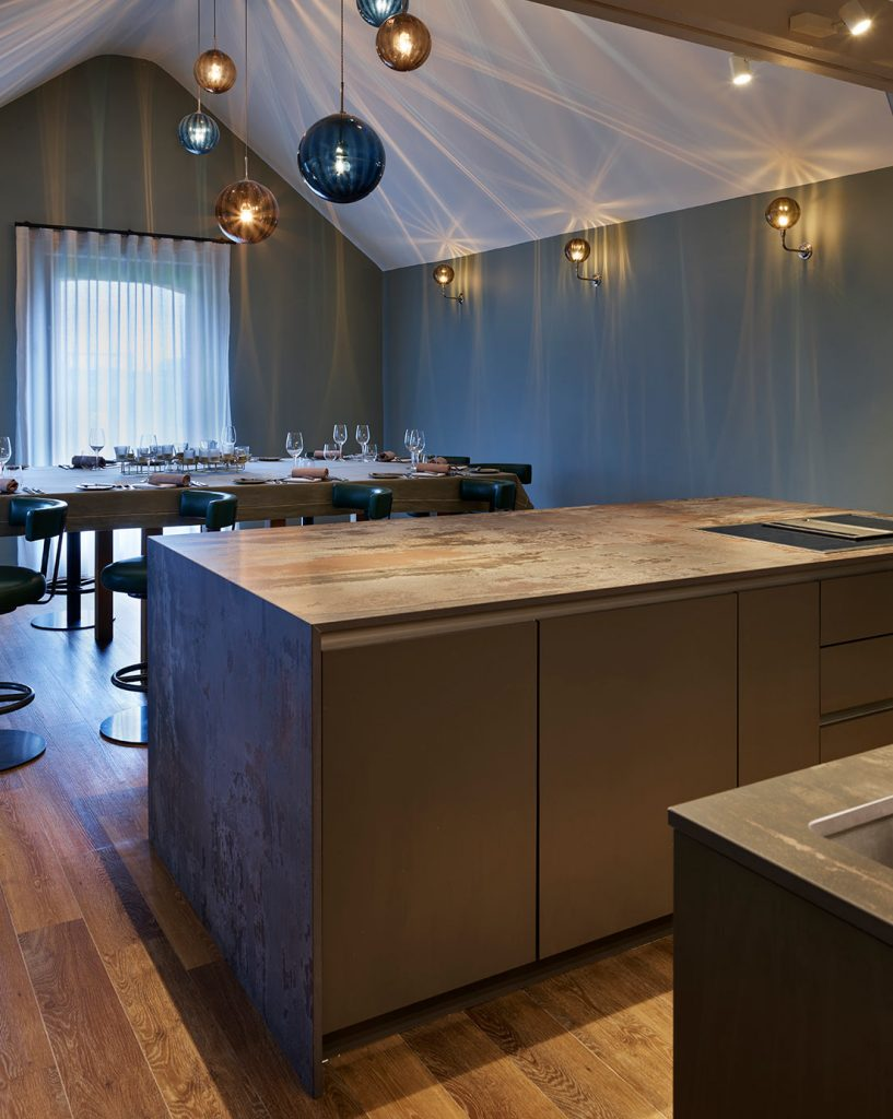 Contemporary kitchen island featuring porcelain worktop and downstands which overlookings dinning table at the woodspeen cookery school in Newbury, Berkshire