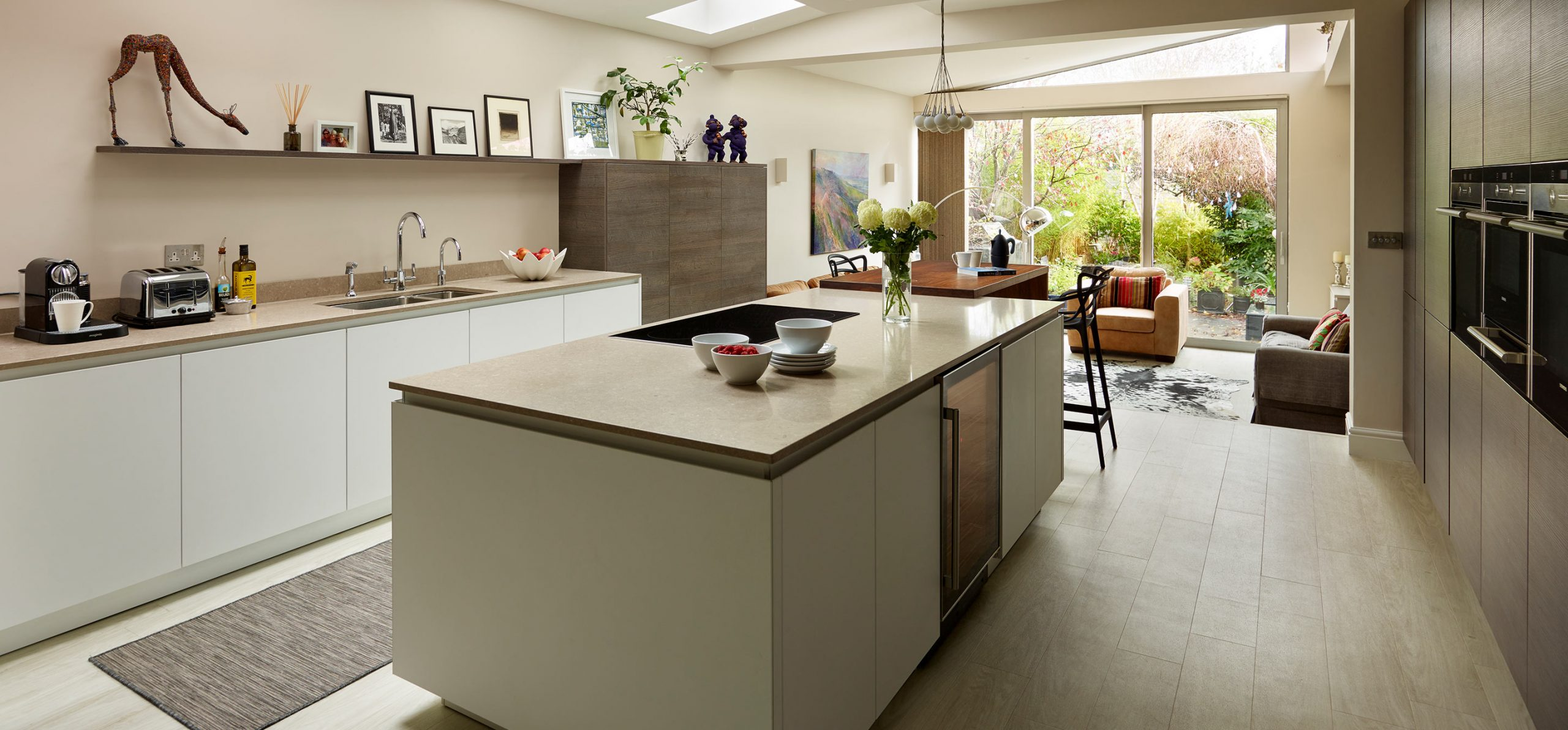 Wide view of modern open plan kitchen in a white base unit finish with light brown porcelain worktops and living space
