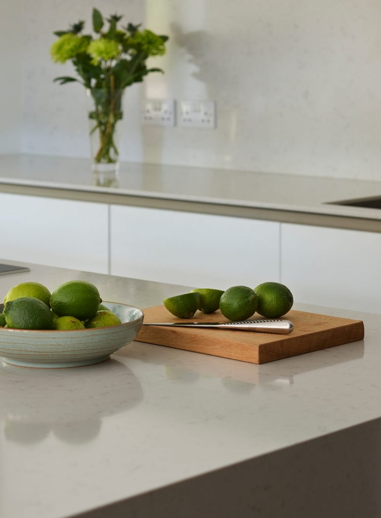 Bowl of Limes positioned on white porcelain worktop with chopping board