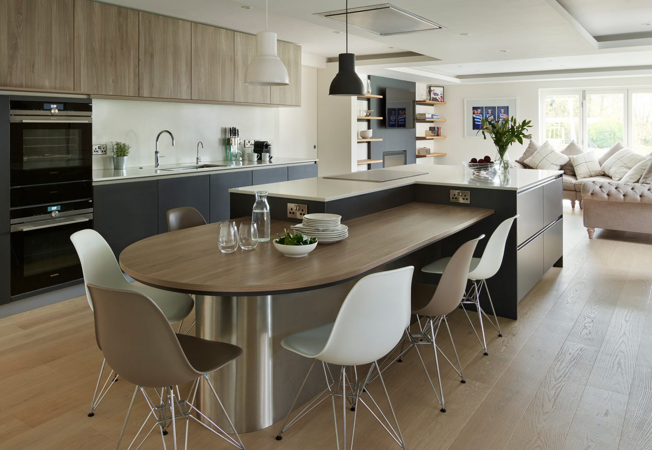 Modern contemporary open plan kitchen space with L shaped island intertwined with casual seating and timber tabletop