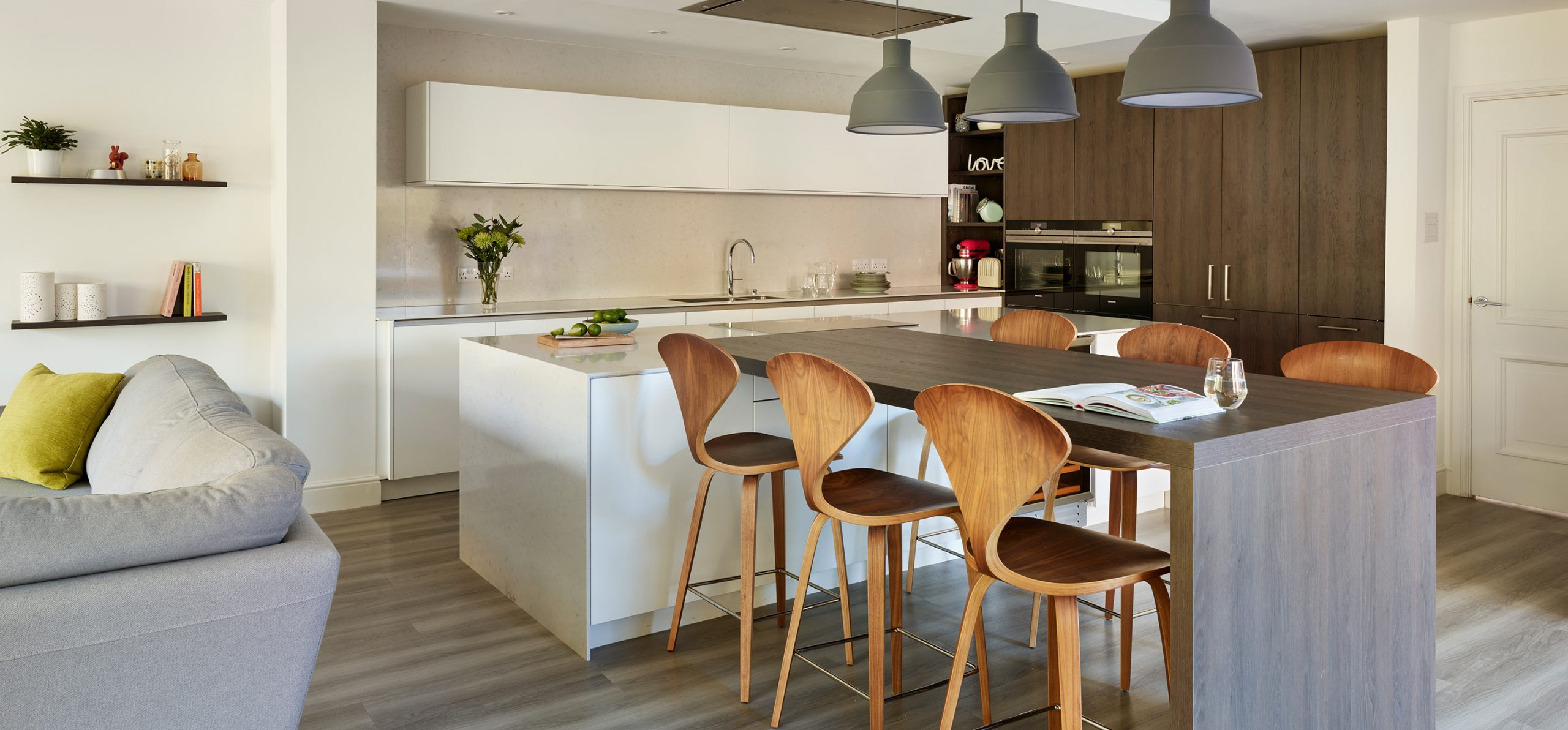 White porcelain island with down-stand's and dark brown timber high tabletop for casual seating