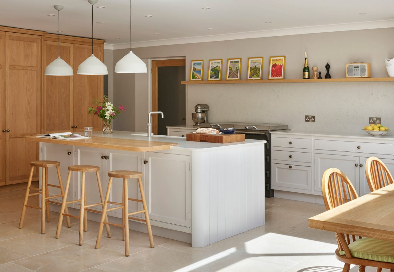 Modern and traditional style kitchen featuring island with composite worktop and oak overhanging casual seating area