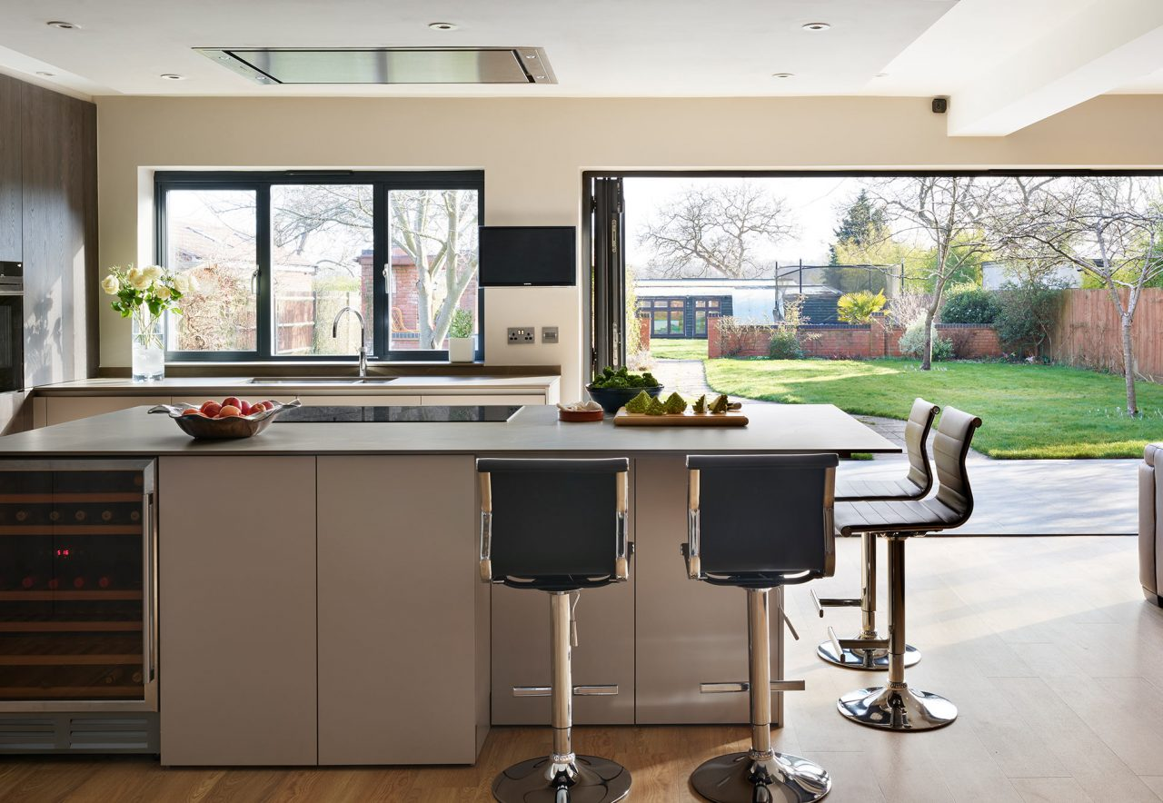Modern, contemporary kitchen featuring island with white units and porcelain worktop and casual bar seating and tall units with built in Gaggenau appliances and a wood finish. All looking out sliding doors onto garden