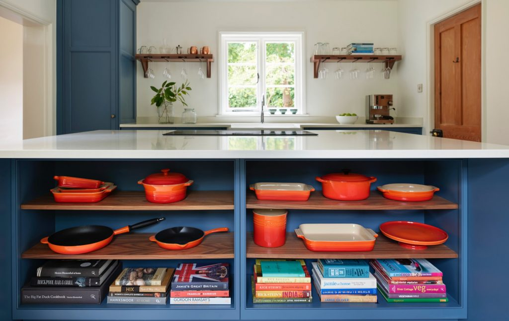 Blue and white under island open walnut shelving displaying pots, pans and books