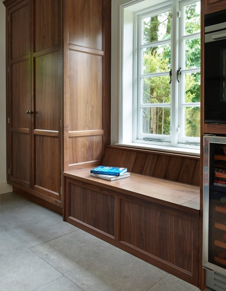 Hand-made tall walnut storage units with multi-functional low storage seating area