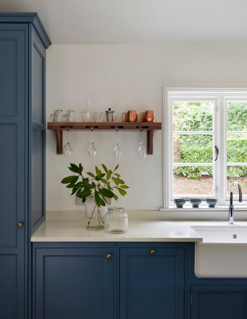 Blue hand-made traditional kitchen with white porcelain worktop and butlers sink with window view